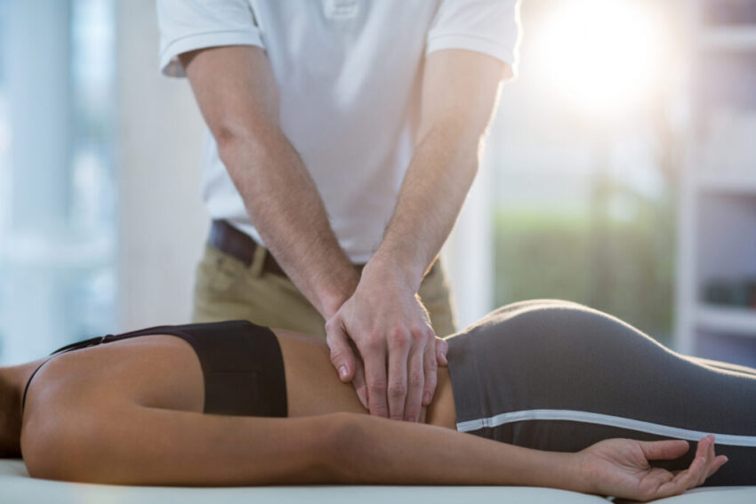 Male physiotherapist giving back massage to female patient in clinic
