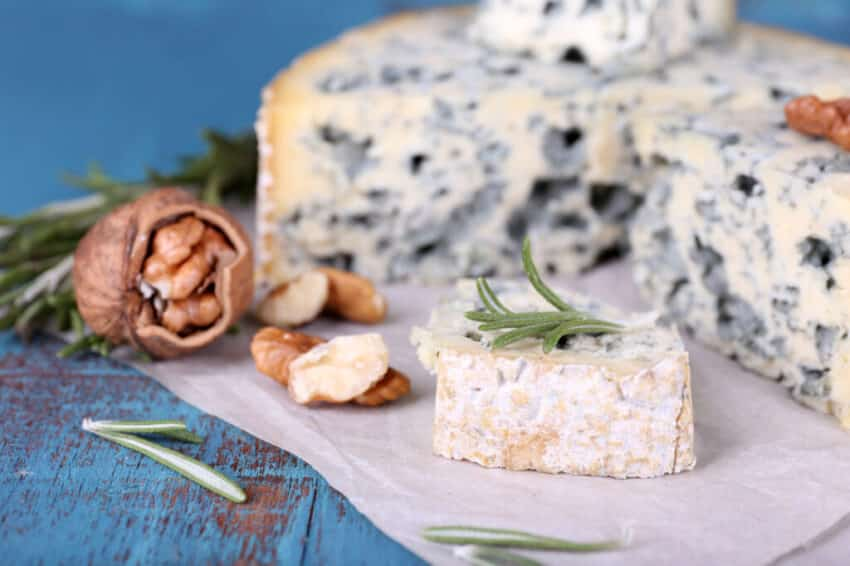 Blue cheese with sprigs of rosemary and nuts on sheet of paper and color wooden table background